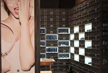 Plastik Kasalar ile Yapılan Ayakkabı Mağazası Tasarımı / Ayakkabı Mağazalarında günümüzde farklı tasarımlar  yaratmak üzerine birçok farklı konsept oluşturulmuştur. Bu tasarımla belirli bir duvar kasalar ile oluşturulmuş ve bu oluşturulurken ahşap beyaz kutular da aralara belirli bir dizilimde sıralanmıştır.Bu ahşap kutuların iç bölümleri ise raf olarak kullanılmakta ve içerisinde ayakkabılar konulmaktadır.