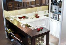 """Кухня """"ГЕРДА"""" / Цветовое решение этой модели сдержанное и строгое, конфигурация фасадов — классическая. Глубокий цвет с патиной верхних секций контрастирует с белой столешницей и белыми фасадами нижних тумб. Барная стойка оформлена витриной со стеклянными полками.   Фасады: массив ясеня, шпон дуба тонированные, патина черная, массив ясеня крашеный;   Корпус: ЛДСП венге, ЛДСП белый, шпон дуба тонированный; Столешница: кварцевый камень; Стеновая панель: кварцевый камень, стекло."""
