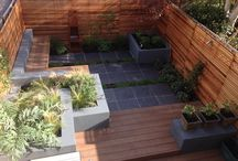 Courtyard Garden designed by Iron Butterfly Design / Courtyard garden in Shirehampton, Bristol featuring interconnected and stand alone raised beds create a series of intimate spaces. Composite decking and slate paving.  Built-in benches, Corten steel fireplace and cedar fencing.  Planting of herbs, Japanese maple, scented climbers and purple and orange flowering perennials.