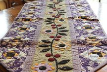 Blackberry Ramble Table Runner Quilt Pattern / Blackberry Ramble Table Runner Pattern is a mixture of cute applique flowers running full length along a central vine, bordered with pieced square in a square blocks. A winning combination of purple, black, taupe and red fabrics have been used.  Finished Measurement 58 inches x 22 inches