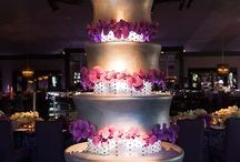 A six-tiered cake covered in silver fondant is decorated with pink and  purple orchids.