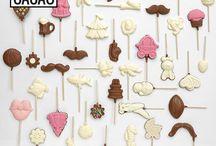 Lollipops / Os nossos lollipops artesanais estão disponíveis em diversos formatos, desde flores, corações, lábios, bigodes, pintainhos e copos de cerveja. Quanto ao tipo de chocolate, a decisão é sua: chocolate de leite, chocolate branco, chocolate com sabor a morango, ou chocolate branco e chocolate de leite. Para além disso, se gostar de crocante, pode ainda optar por topping de pintarolas ou açúcar colorido.