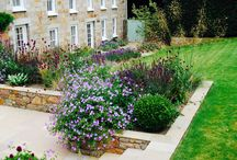 Jersey Garden / A garden I designed in 2012 using raised beds built out of the local pink granite, a patio and steps and lush, colourful herbaceous planting.