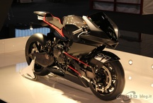 VYRUS 986 M2 / The 986 M2 has a 'funny' front end, among other technical innovations, including a laterally-mounted F1-style rear shock, underslung radiators, an 'omega' frame (using the engine as a stressed member) and a carbon-fibre monocoque tank and seat unit.  There are no telescopic forks, just a collection of rods, levers and rose joints connecting handlebars to the front wheel spindle.  www.vyrus.it http://www.facebook.com/vyrus.motori