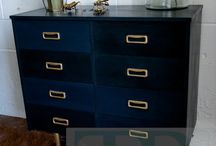 """""""One Dark Mid Century Evening"""" / We like to describe this as mid century modern with a neo classical twist and maybe a slight touch of medieval. This collection combines dark rich colours  with each piece hand painted in varying mixes of Graphite and Napoleonic blue. Gold accents through gold gilding (using Annie Sloan's gold sizing)  as well as gold stud work and stencilling. This collection has been created using Chalk Paint™ by Annie Sloan."""