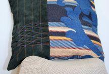 """Kussens """"smok"""" en """"kabel"""" / Lederen kussens gesmockt en versierd met een gebreide kabel."""