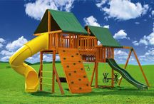 Fantasy Swing Sets / The Fantasy Swing Set #1 features two clubhouses (a 5 1/2' and 7' high), the 7' Deluxe Rock Wall and the 7' Spiral Tube Slide and Steel Rung Access Ladder. Our exclusive design includes a bridge that doubles as a viewing deck while connecting the two clubhouses. Our design also incorporated a Double Wide Monkey Bar with a 3 Chain Tire Swing and a Gym Ring/Trapeze bar Combo under the 7' tower and bridge! What a great way to save space and add activities.