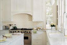 White Kitchen Favorites / Interior Design White Kitchens, culcutta gold marble,  glass backsplash, dark hardwood floors, stainless steel appliance, over lay cabinets, in-set cabinets, raised panels