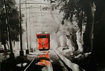 Kolkata City Escape / Kolkata Cityscape , a popular series by contemporary artist Arpan Bhowmik depicts the famous Trams in Kolkata against a backdrop of the city . These paintings take you back in time. A work in acrylic on canvas , the series is much admired and wide selling.