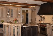 Kitchens With French Provence Design Influence / Kitchens with cozy, old-world French provence influence inspire one homeowner with European roots. Carved posts, stained ceiling beams and painted distressed wood cabinetry set the stage for a gourmet cook's kitchen renovation. Hand-made porcelain and clay tiles for the backsplash and a patterned granite for the countertops complement stenciled hardwood flooring and the high-end appliances selected for this kitchen.
