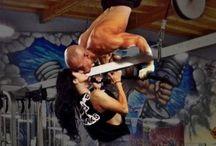 """Kalistenika / Kalistenika (stgr. καλὸς σθένος kallos sthenos – """"piękno i siła"""") – aktywność fizyczna polegająca na treningu siłowym opartym o ćwiczenia z wykorzystaniem własnej masy ciała, takie jak np. """"pompki"""", """"mostki"""", """"brzuszki"""" i """"dipy"""". Jest często łączona ze stretchingiem."""