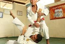 """Sports / O jiu-jitsu ou jiu-jítsu (em japonês 柔術, transl. jū, """"suavidade"""", """"brandura"""", e jutsu, """"arte"""", """"técnica"""")[a] é uma arte marcial japonesa, porém de origem indiana, que utiliza alavancas e pressões para derrubar, dominar e submeter o oponente, tradicionalmente sem usar golpes traumáticos, que não eram muito eficazes no contexto em que a luta foi desenvolvida, porque os samurais (bushi) usavam armaduras."""