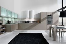 Emi / A young kitchen with a futuristic design. Modular solutions creating spaces where living room and kitchen permeate each other, embracing the new trend. A minimalist project embodying the ultimate trend: young and light. Emi is definitely hi-tech thanks to its colours.
