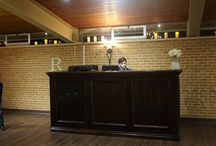Reception Hall / The Reception Hall is lit with old world style chandeliers & pendents on the walls & a cascade of lights strung across wooden ceilings. It is equipped with a custom built bar, DJ booth, slide show tvs.