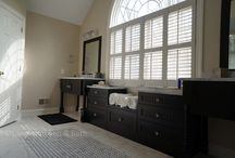 Master Bath with a View in Doylestown, PA / This master bathroom design in Doylestown, PA utilizes the large window as a central feature and a source of natural light.  The black vanity cabinets are built on either side of the window with a window seat and more handy storage underneath.  White tiles and a marble countertop contrast beautifully with the black cabinets, and the glass shower enclosure adds to the bright atmosphere of the design.