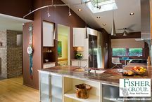 HOME REMODEL: Designed for Art - Contemporary Kitchen / Truro. Annandale. Virginia. Removing the wall between the kitchen and the adjoining areas and raising the ceiling gave a spacious feel.   The new kitchen was planned to give pride of place to the sculptural hood vent and the wife's paintings.  High gloss cabinets and maple flooring accompany the stunning granite countertop which flows across the peninsula in a sweeping gesture of welcome. Swirling stainless steel track lighting completes the space.