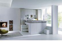 """Dal letto contenitore al """"Container-letto"""". / Un letto posto nella parte alta consente la formazione di uno spazio a camerino ricavato sotto il piano letto, sollevabile per un facile accesso. Più di tre metri cubi di spazio in più da organizzare liberamente. Container permette di recuperare quattro metri quadrati di spazio che si trasformano in ben 3,2 metri cubi di contenimento Disponibile in tutti i colori di struttura ed EcoLegno con possibilità di inserti laccato colore. L'interno è disponibile in nobilitato bianco."""