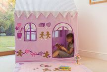 Gingerbread Cottage Playhouse / Soft lilac playhouse almost good enough to eat with cute applique and embroidered gingerbread men (and women!) adorning all four sides. Featuring pretty lilac ribbon, pink bows and scrummy heart shaped biscuits. Turn the playhouse around and it becomes a Sweet Shop with its own door and shelves depicting icing full of tasty treats including traditional candy canes and swizzle lollipops. Ideal for playrooms and bedrooms, available in a small and large size.