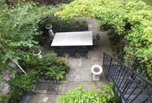 Project Regent's Park House / www.aralia.org.uk A basement courtyard garden reached from the first floor via an iron stairway. Shade is provided by a metal arbour, beneath which sits a stone table, urns and metal chairs. Natural flagstones continue the traditional theme and the whole feeling is one of shade and coolness.