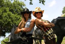 Pioneer Plaza Cattle Drive in Dallas, TX / Two girls having fun modeling cowgirl hats among bronze cattle and cowboys