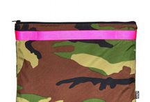 ANDI Too / Originally conceived as a shoe bag, the classic shape and industrial lining of The ANDI Too affords a variety of uses as an additional internal or external compartment, or a standalone clutch with an accented handle. Accented by its prominent partner in chic edgy excellence, the Camo ANDI Too is lined and strapped with a vibrant fluorescent pink pop.