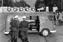 """Lautsprecherkrieg im geteilten Berlin / Mit dem Mauerbau 1961 ging der Kalte Krieg in seine frostige Phase über und wurde in Berlin per Dezibel mit Lautsprechern ausgetragen. Mit immer größeren Beschallungsanlagen versuchten Ost und West, sich gegenseitig mit immer lauterer Propaganda zu übertönen. Vor allem die Berliner Bevölkerung, die nahe der Mauer wohnte, litt unter der lauten Kriegsführung, die die Propagandaeinheiten """"Studio am Stacheldraht"""" (West) und """"Studio 13. August"""" (Ost) veranstalteten."""