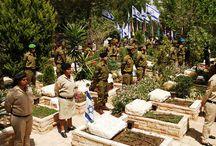 IDF żołnierze stoją na baczność przed grobami żołnierzy IDF