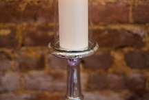 "Unity candle / The unity candle ceremony uses two taper candles with a large pillar candle (called the ""unity candle"") in the center. At the beginning of the wedding ceremony, a representative from each family (usually the mothers of the bride and groom) light the two taper candles. Later in the ceremony (usually after the formal vows), the bride and groom use the two taper candles to light the large pillar (unity) candle together."