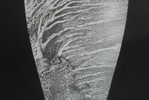 """EXPOSICIÓN """"LITHOGRAFISMOS"""", FABIÁN CASTILLA / A través de la cerámica y el grabado, del fuego y las entrañas corrosivas del ácido, el artista nos muestra su visión personal de nuestro paisaje. Coladas, alisios, mar de nubes, agua, etc,… modelan y caracterizan nuestro entorno. El negro luminoso de las lavas sobre el blanco cegador del barro y el papel."""