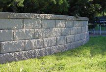 Støttemur Smaragd / Smaragd har brukervennlige murblokker som er både lette å løfte og legge. De rundknekte blokkene bygger en livfull muroverflate som med fordel kan belyses med vår lettmonterte toppbelysning. For å avlutte muren brukes Brilliant Topphelle. Muren har en innebygd helling på 4 grader.  Smaragd kan bygges opp til 1,05 m uten jordarmering. Låsetappene på baksiden av blokkene gir muren stødighet, og derfor behøves ikke muring eller andre sikkerhetsforanstaltninger. Minste radius er på 1,2 m.