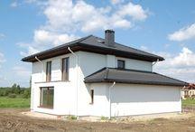 Projekt domu Szmaragd / Projekt domu Szmaragd to jeden z najnowszych projektów domów jednorodzinnych. Nowoczesna forma budynku z atrakcyjnymi detalami współgra w nim z prostą formą zbudowanej na planie kwadratu bryły, przekrytej kopertowym dachem. Zasadniczą bryłę domu wzbogacono o częściowo wystający garaż, podcień wejściowy i ogrodowy, wykusz i balkony.