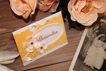 Collezione OPHELIA / Caratteristiche: Bordatura ondulare, cartoncino martellato, fiori e foglie tridimensionali, cornice ovale, strass arancioni, paillettes gialline multicolore, decori a rilievo