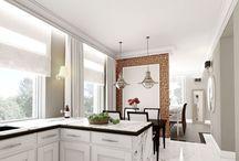 PROJEKT REZYDENCJI W OZAROWIE / Aranżacja białej kuchni z ceglaną ścianą i chromowanymi loftowymi lampami nad stołem w jadalni. Blat wykonany jest z białego konglomeratu z wzorem kamiennym i wykończony drewnianym profilem od spodu, aby dodać mu dekoracyjności.