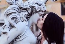 people kissing statues