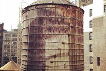 Water Tanks / Years ago when I lived and worked in New York City, the lunch room of my work on 5th Avenue & 18th street overlooked the tops of many buildings where I became fascinated with all the old water tanks ( often wooden dinasours).