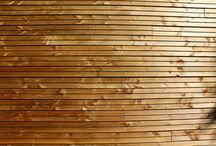 Maison TL / Maison contemporaine à étage de 116m².  Un séjour avec une cuisine ouverte, un cellier, deux chambres, une salle d'eau et un WC séparé en bas.  A l'étage la suite parentale, avec un grand dressing, une salle d'eau et une terrasse sur le toit du séjour.  La maison est chauffée avec un poêle à granulés. Les menuiseries sont aluminium gris anthracite.  La toiture plate est recouverte d'une membrane d'étanchéité grise et des acrotères.  Le bardage est en douglas horizontal faux claire-voie marron.