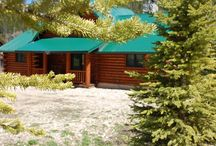 River Chant Lodge / A Pure, Luxurious Log Home that OVERLOOKS THE RIVER with a PRIVATE HOT TUB!!!  3 bedroom/2-1/2 bath cabin with a spacious living room with a fireplace, large plate glass windows, TV/satellite, wi-fi, washer/dryer, hot tub, 1/2 bath. Master has a king bed, private bath with access to the adjoining wrap around deck. Upstairs in the loft, are four twin beds. Downstairs are 2 guest bedrooms one with a king bed the other with a queen, a bath, an office space, additional sitting area and fireplace