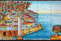 Amalfi Coast Ceramic Backspash Murals / The beautiful scenery of Amalfi Coast has been hand painted into one collage on ceramic tiles that will make your home more unique. Here you will find a variety of unique murals that are our own creations or you can submit your own custom picture for us to paint on the tiles. You will find home décor such as small tiles, plates to hang on the wall along with vases and bells for decoration (upon request) as well as larger tiles that would look stunning in an entryway, or garden.