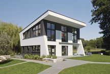 Individuell geplantes Ausstellungshaus Linx / Lebensqualität und Komfort geben hier den Ton an, visuell umgesetzt in frischem, neuartigem Architektur-Design. Grenzenloses Raumgefühl entsteht durch gezielt gesetzte Geschosserhöhungen, innen verarbeitete Optiken in Schieferfarben und Betongrau, eine komplette Küchenwand in Tafellack. Dies alles unterstreicht den urbanen Loftcharakter des Hauses, der dennoch stets den Wohlfühlfaktor ins Zentrum rückt.