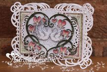 Romantique Garden Collection / The Romantique Garden collection is a romantic symphony composed in subtle shades of pink, fuchsia, green, cream and charcoal harmonizes beautifully with picturesque images of dainty hummingbirds, devoted love birds, graceful swans and delicate bleeding heart bushes.  The coordinating die cuts feature elegant swirled stems, a graduated set of bleeding heart blossoms and a majestic pair of swimming swans.