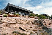 Arte sobre la colina / Esta casa modular de diseño se encuentra posicionada sobre una pequeña colina de la zona rocosa. Las estructuras metálicas que crean a los módulos, se encuentran sostenidas sobre pilotes.