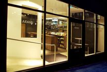 Arami — NWD / We were commissioned to design the interior for Arami, a Bangladeshi restaurant. Arami's beautifully presented food deserved an equally considered setting. A difficult space was divided into a restaurant space and a cosy bar area. We used tilted mirrors to reflect the goings-on around you as you eat, while cool greys, warm chocolate and subdued lighting made this interior stand out in Newcastle's crowded curry house market.