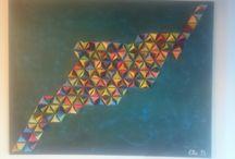 Tableau origami coloré / Des origamis en forme de pyramide, collés et peints sur un tableau.