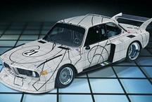 """BMW Sanatsal Otomobiller #2 BMW 3.0 CSL '76 / 1976 yılında ABD'li ressam ve gravür sanatçısı Frank Stella'dan BMW Sanatsal Otomobiller Projesi kapsamında BMW 3.0 CSL'i boyaması istendi. Tasarımında siyah ve beyaz kareli desen kullanan sanatçı, bu geometrik kesimlerle de optik açıdan ilginç bir çalışma ortaya koydu. Bu model aynı zamanda """"24 Saat Le Mans Yarışı""""na da katıldı."""