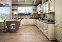 Idee per la cucina in legno / Abbiamo scelto Magda, una delle nostre belle cucine in legno, proponendola in diverse cromie e in originali composizioni. Abbiamo inserito elementi a giorno, componenti living, muretti in pittura. Abbiamo creato inusuali e straordinari abbinamenti con modelli dai tratti contemporanei, accostando il legno al colore laccato. Quelli che vi proponiamo sono solo alcuni esempi di come lo stile diventi unico per ogni singola cucina che viene progettata, scelta, vissuta ed amata…