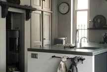 Landelijke keuken / Landelijke grijze keuken met betonnen aanrechtblad. Muur met paneeldeuren en stoere schouw met gaskachel. Vloer van estrikken tegels. De keuken is sfeervol gemaakt met stoere, sobere landelijke accessoires.