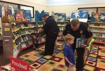 Officers carry books to give to children / Some officers carrying books in cruisers for children