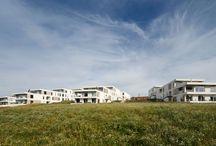 RAVN_Juulsbjergparken / Juulsbjergparken er beliggende i det naturskønne og kuperede landskab i Bredballe ved Vejle. Boligerne består af rækkehuse i to etager og terrassehuse – alle med sydvendt terrasse  Bebyggelsen er visuelt integreret i landskabet med sedum på tagfladerne – og alle boliger har let udgang til de grønne områder mellem husene.  Arkitektonisk fremtræder boligbebyggelsen enkel og lys. Bebyggelsen rummer boligtyper i både ét og to plan.