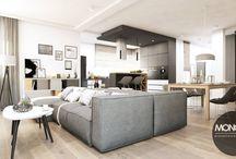 Minimalistyczny dom pod Krakowem / Nasz najnowszy projekt to minimalistyczne połączenie głównie dwóch kolorów: bieli i szarości. Całość ociepliliśmy podłogą z deski i drewnianymi elementami w postaci stołu czy szafek. Charakteru całemu wnętrzu nadaje nowoczesny kominek z czarnym akcentem kontrastujący ze ścianą oraz wszelkie dodatki, od tkanin aż po drobne grafiki.
