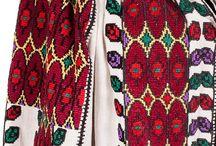 """Colecția """"Flori de IE"""" / Colecția """"Flori de IE"""" numără câteva zeci de costume populare românești vechi de la câteva zeci de ani, la o sută și chiar mai mult.   Fiecare IE este realizată integral manual, pe pânză de bumbac, cu broderii ample și bogate, în culori vii, având adesea aplicații de mătase, paiete sau mărgele. Iile au fost restaurate, analizate și certificate de către un expert etnograf, tocmai pentru că ia românească nu reprezintă doar o simplă lucrătură manuală în culori."""
